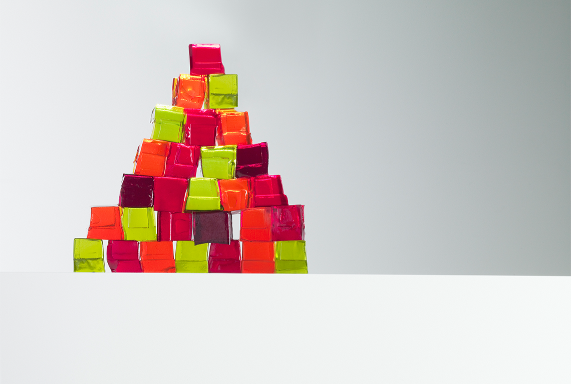 a triangular stack of differently-colored jello cubes against a white background. they look delicious.
