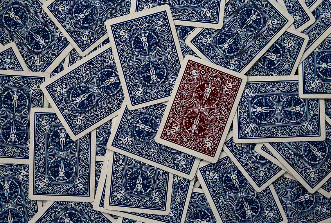a bunch of blue playing cards with one red card amongst them. it stands out
