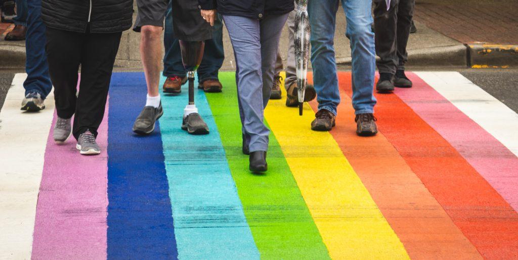 A crowd of diverse men and women walking across a rainbow-colored crosswalk.
