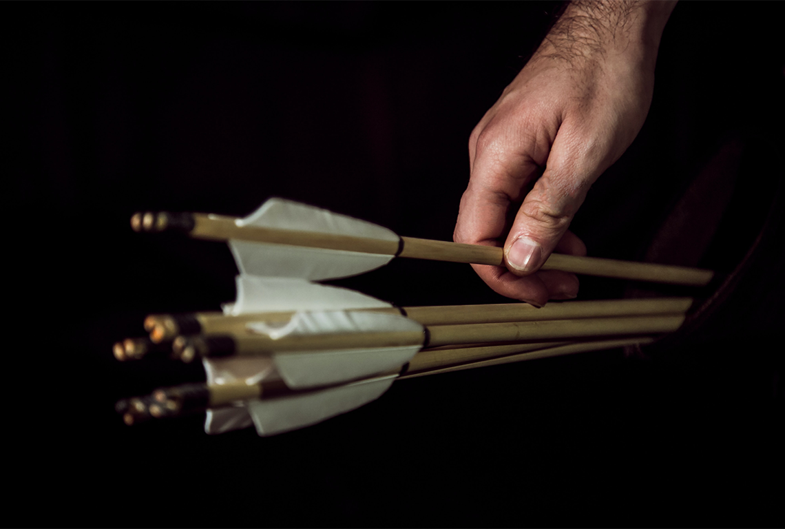 A hand reaching for a bundle of arrows, like the kind that are fired from a bow.